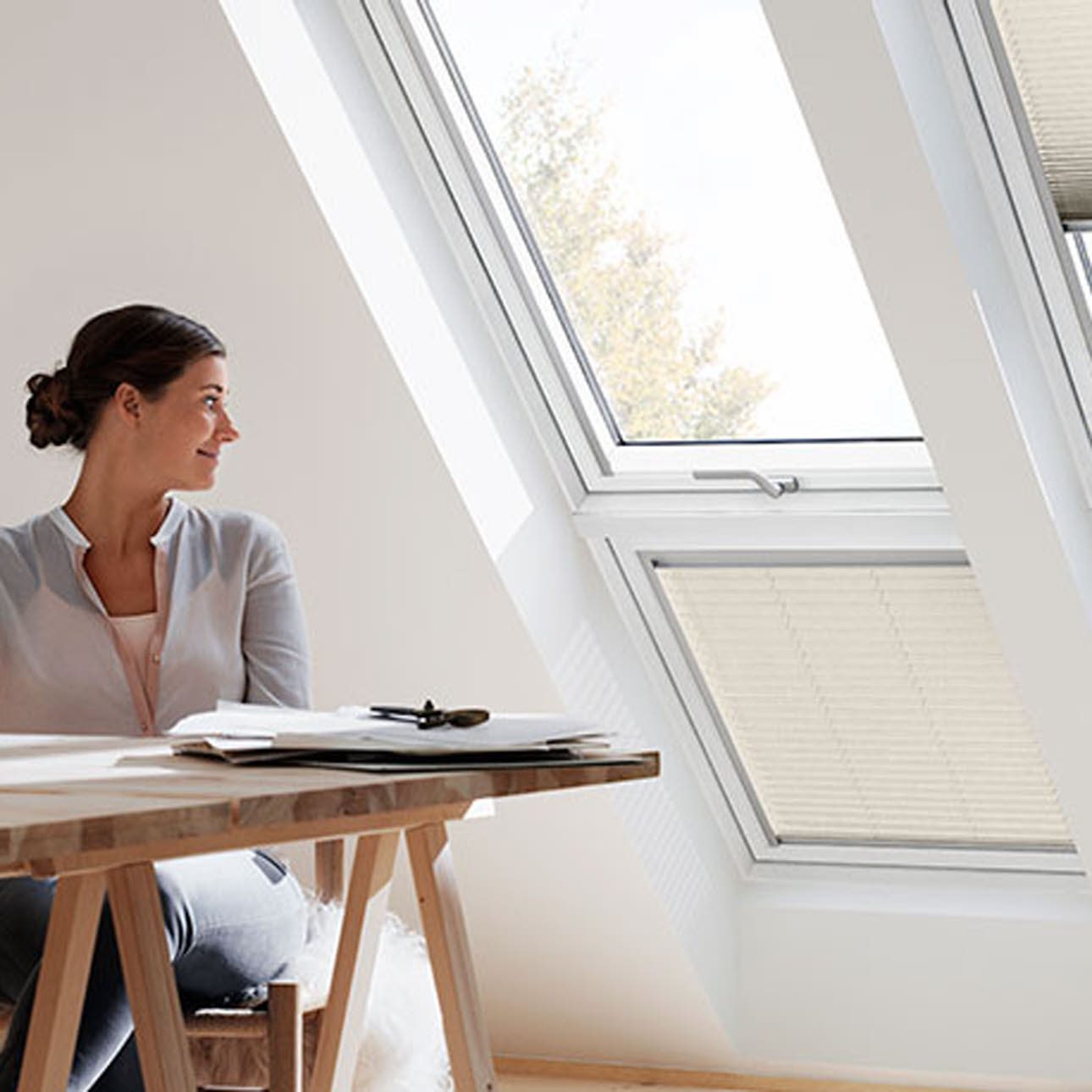 Woman gazing out of sloping double combination Velux window