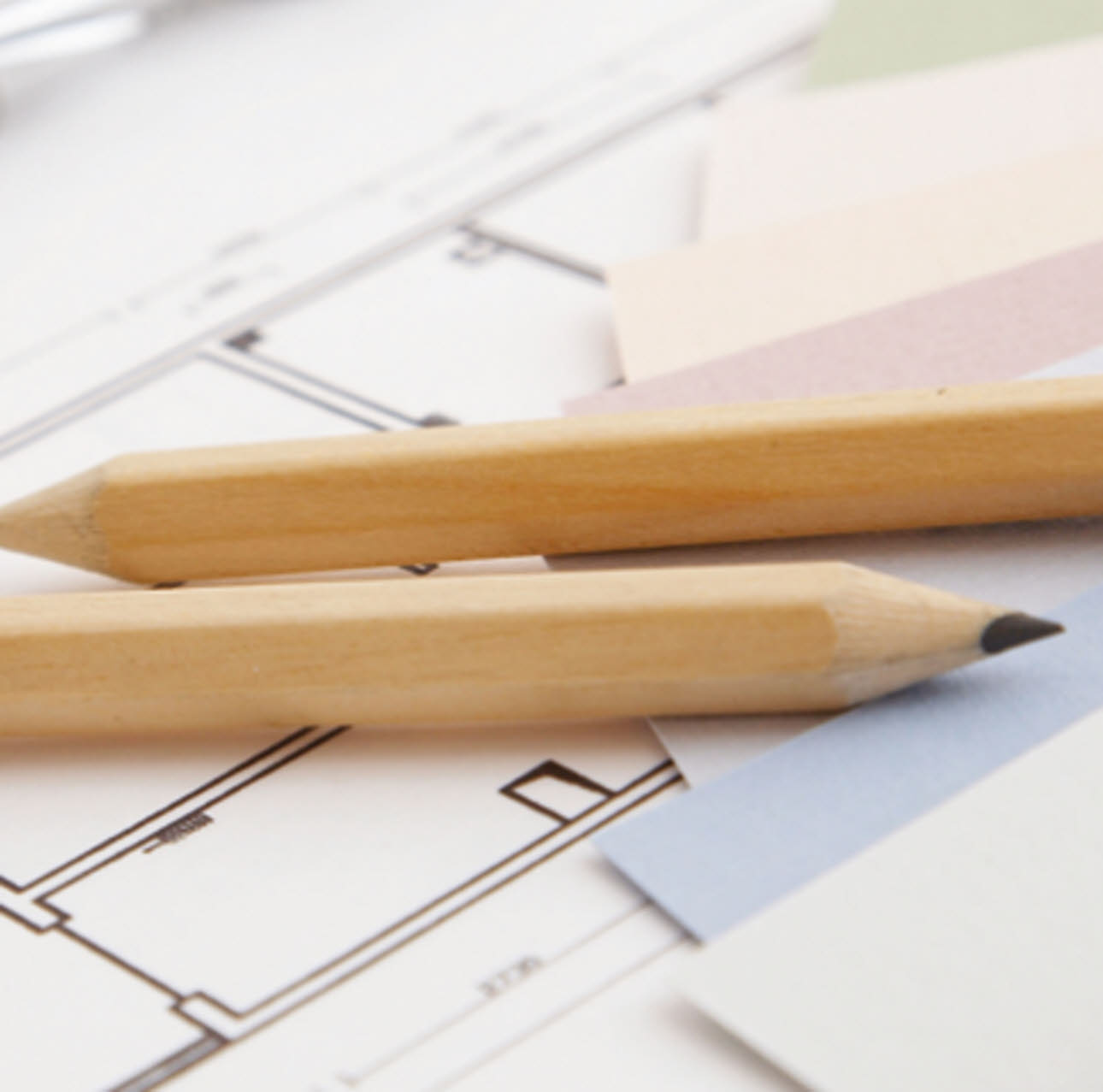 Two pencils placed on top of kitchen design plans