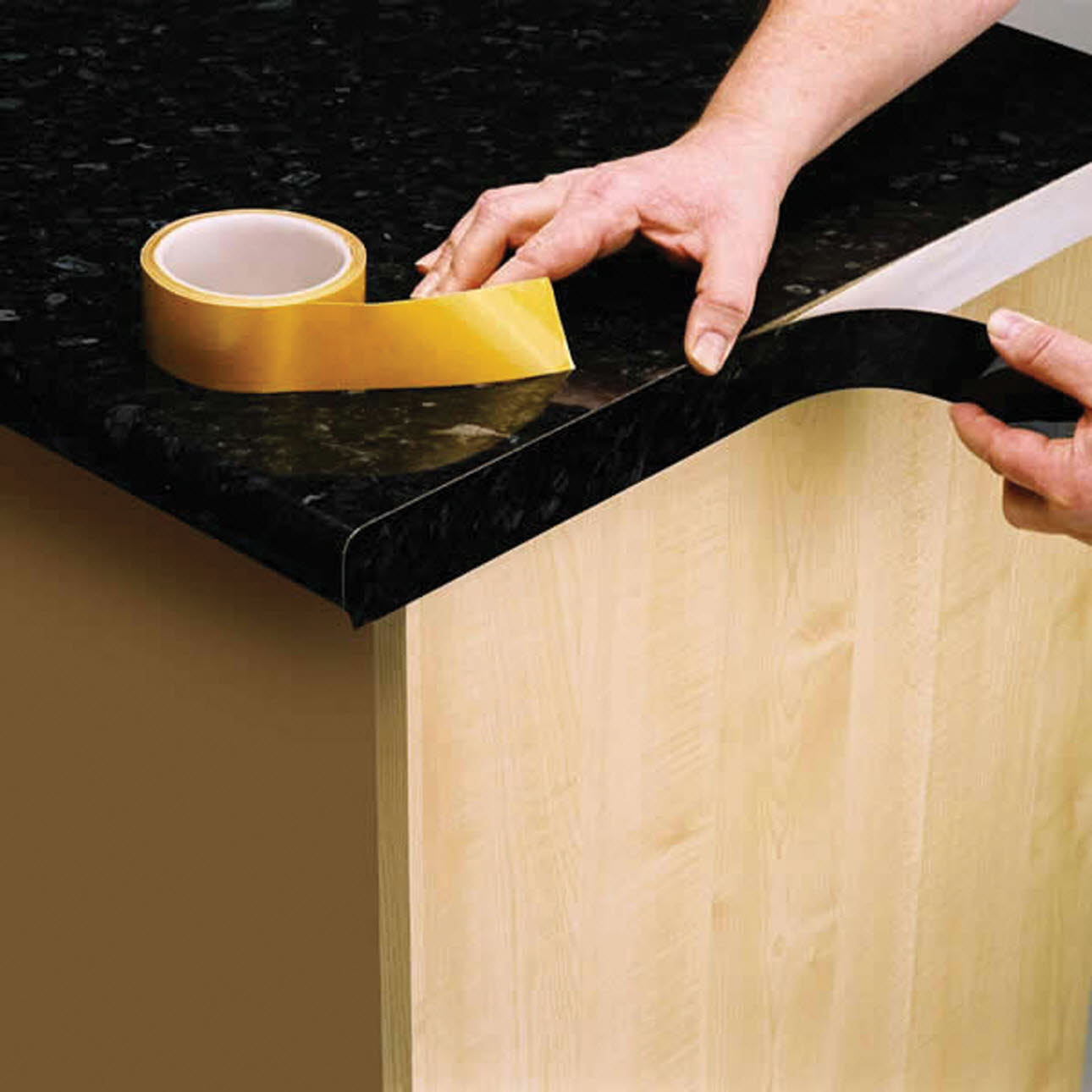Yellow adhesive tape, placed on black kitchen worktop during installation