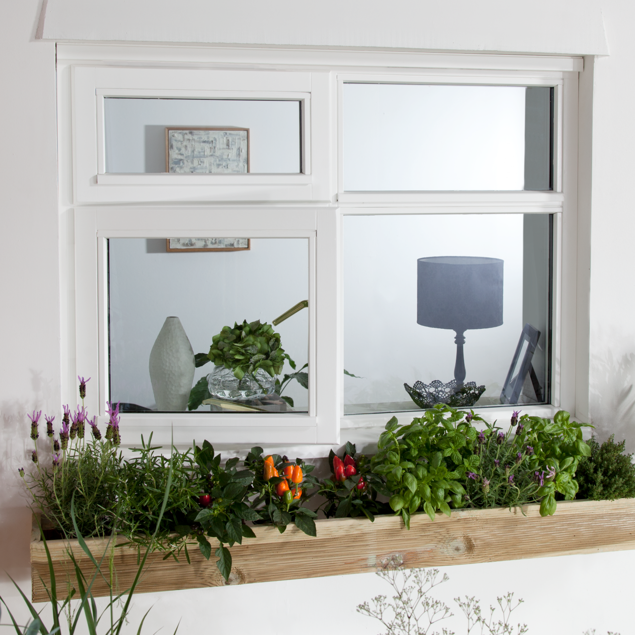 Exterior shot of square UPVC window, with window box full of flowers below