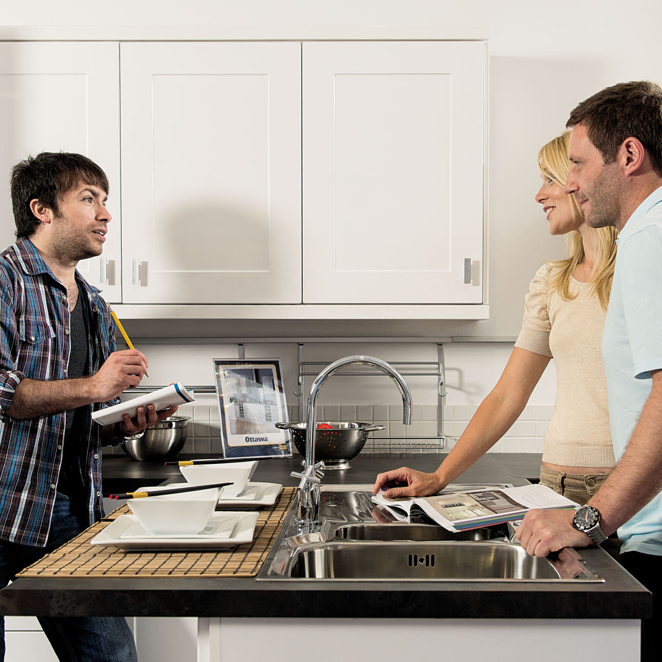 Kitchen designer discussing designs with couple leaning on kitchen island with sink