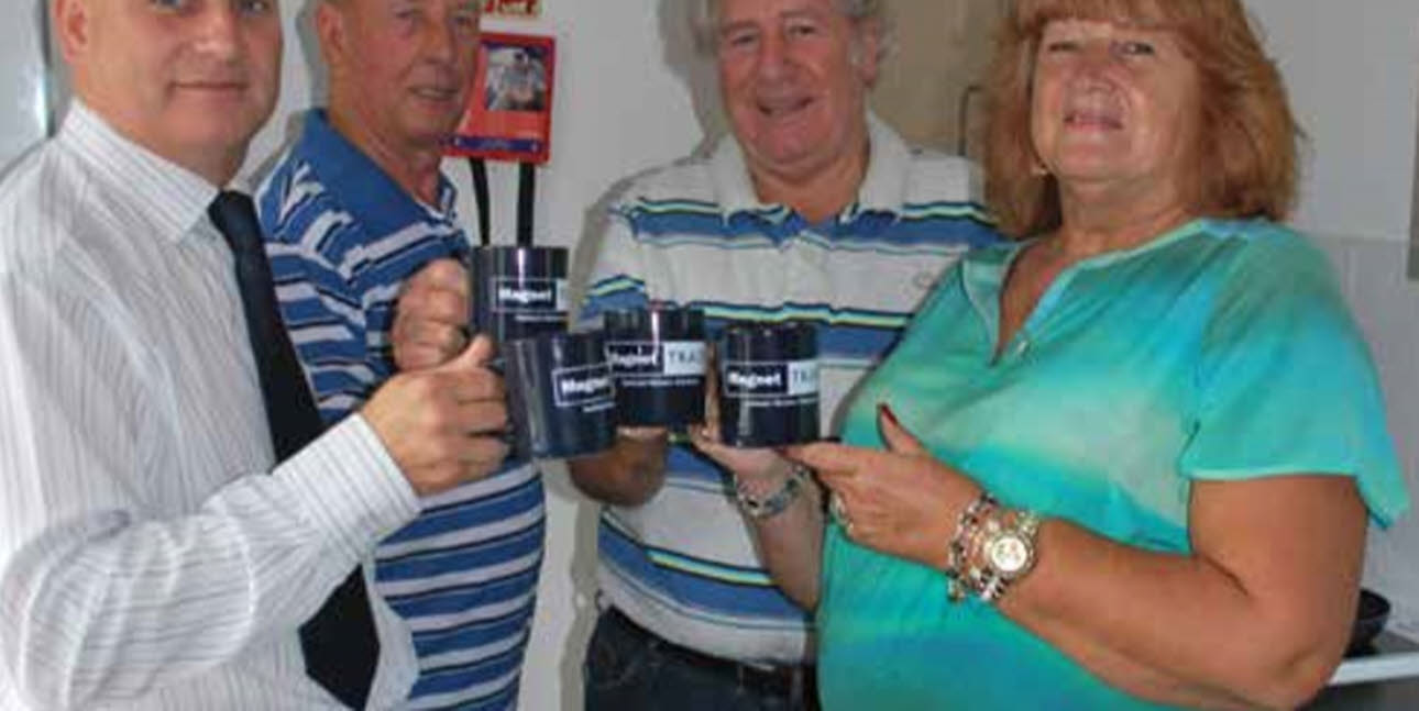 Four Magnet Trade employees, holding Magnet Trade mugs