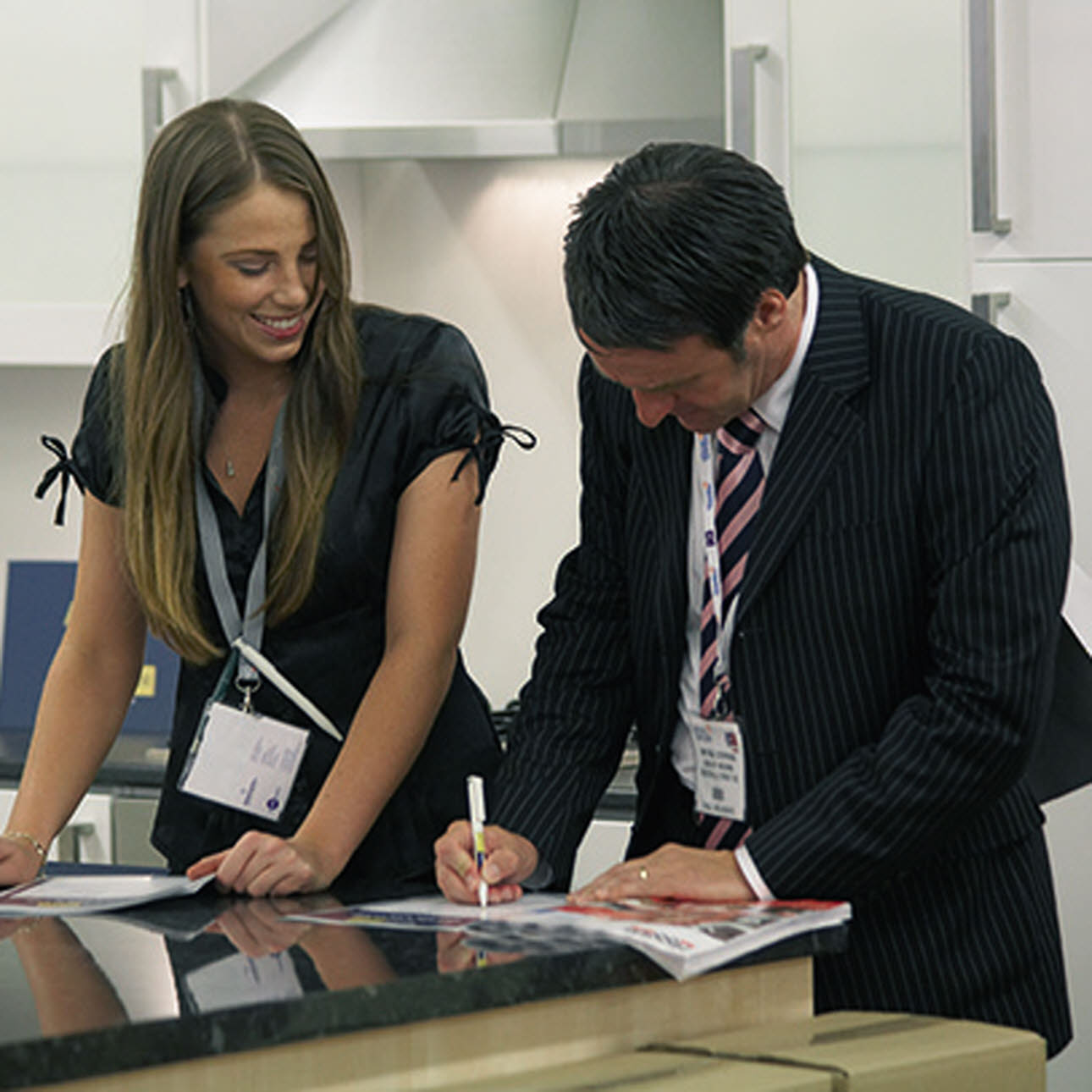 Man & woman deciding on kitchen designs in showroom