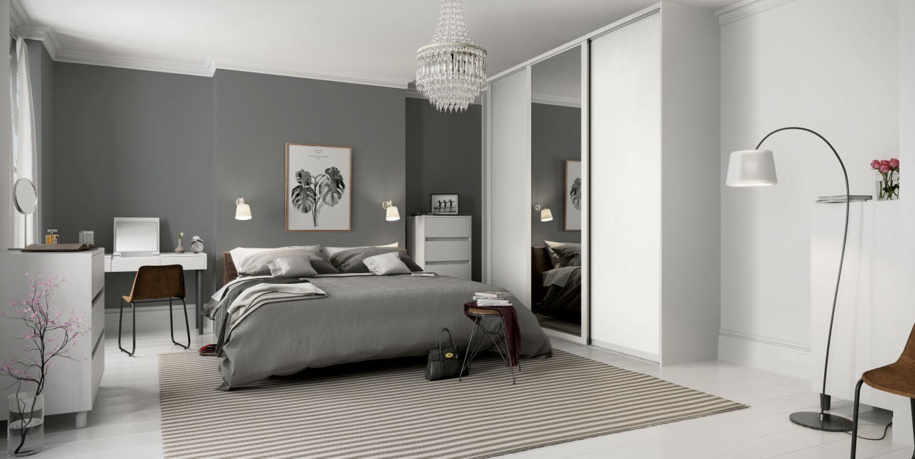 Grey bed and white fitted bedroom wardrobe with single full length mirror