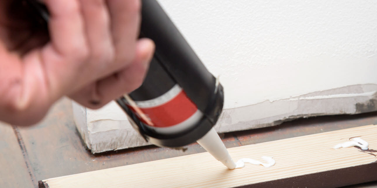 Close up of Silicone adhesive being placed on back of brown skirting board to be installed, grey floor