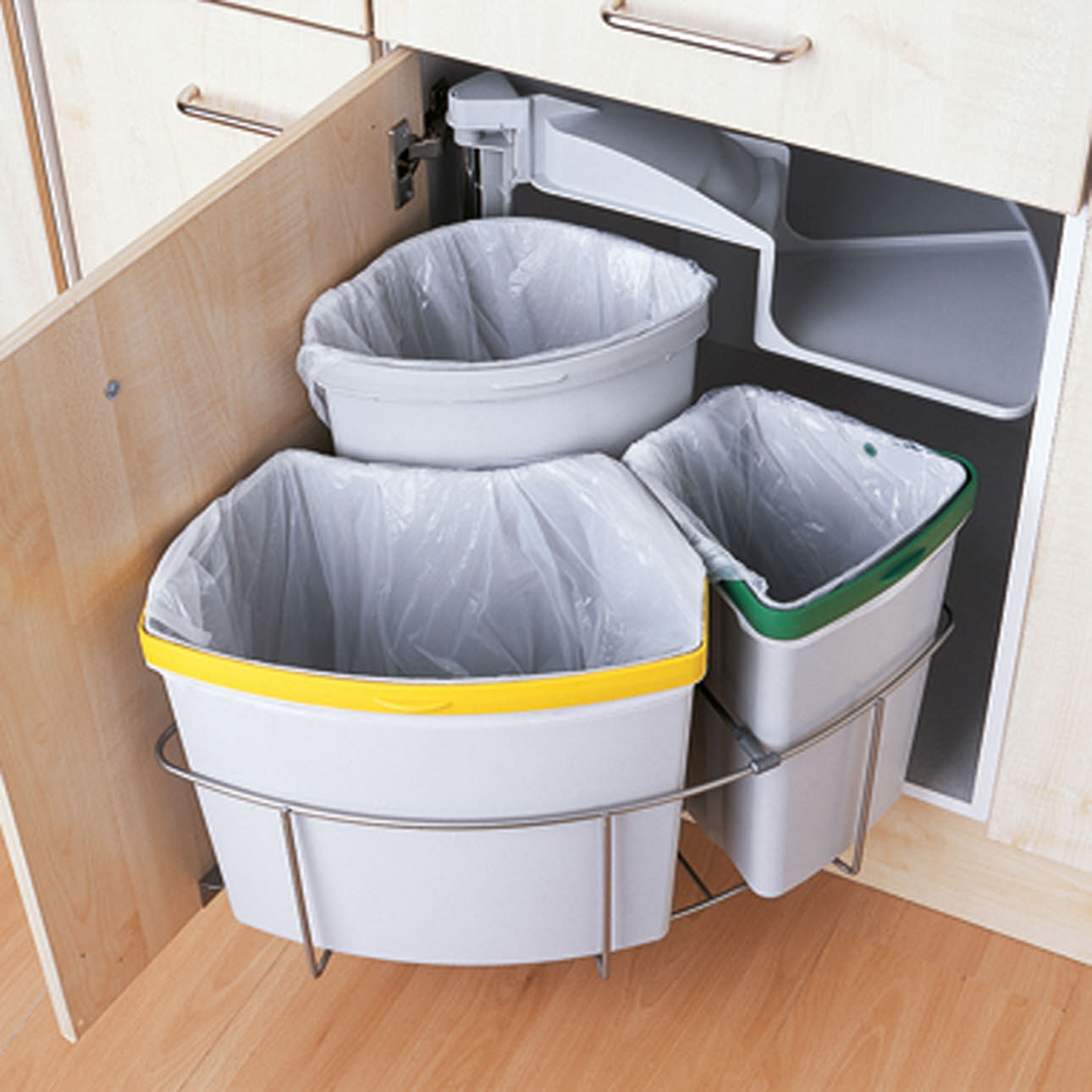 Three fitted waste bins inside kitchen unit, door open