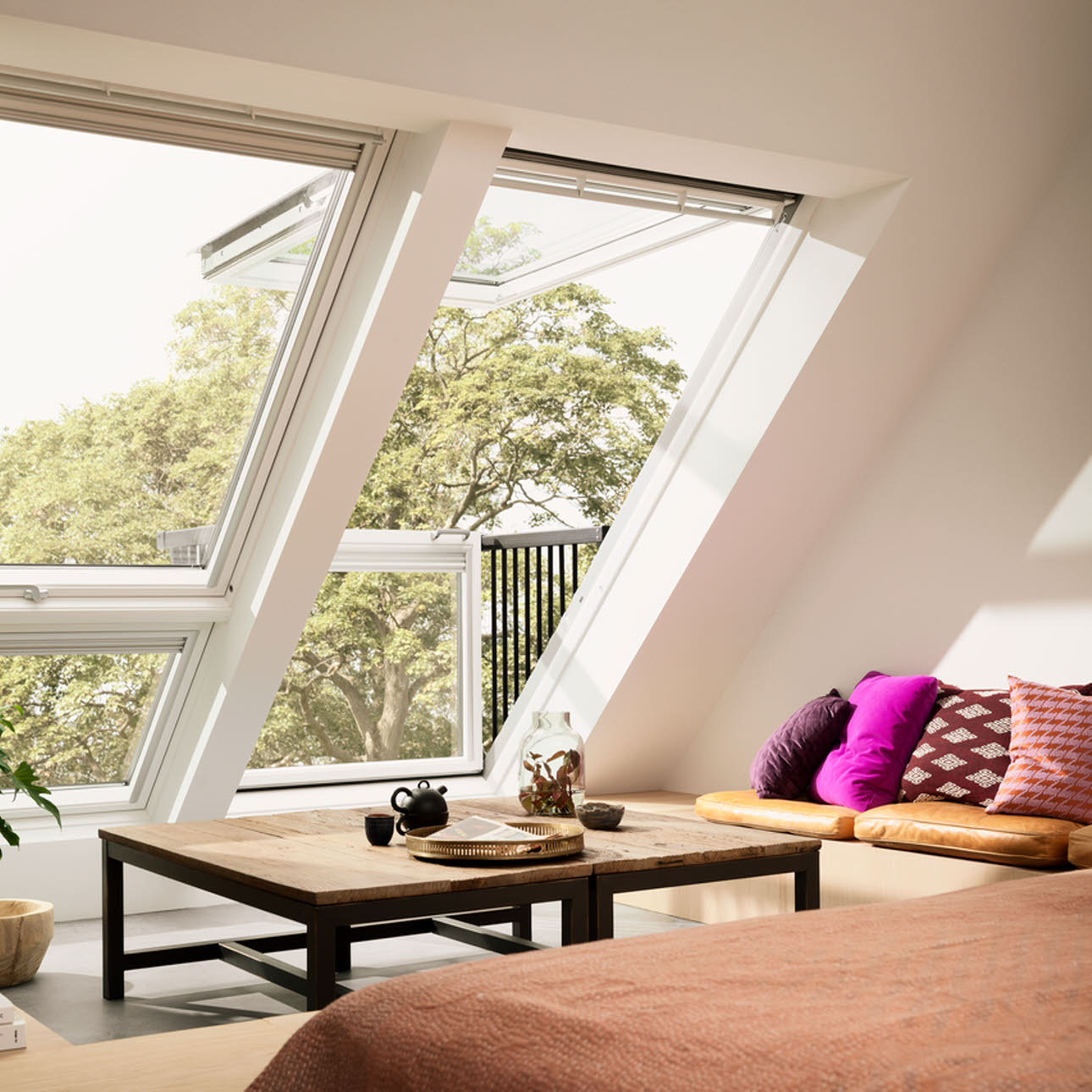 Large living room Velux window opening out onto balcony, wooden coffee table and covered brown sofa