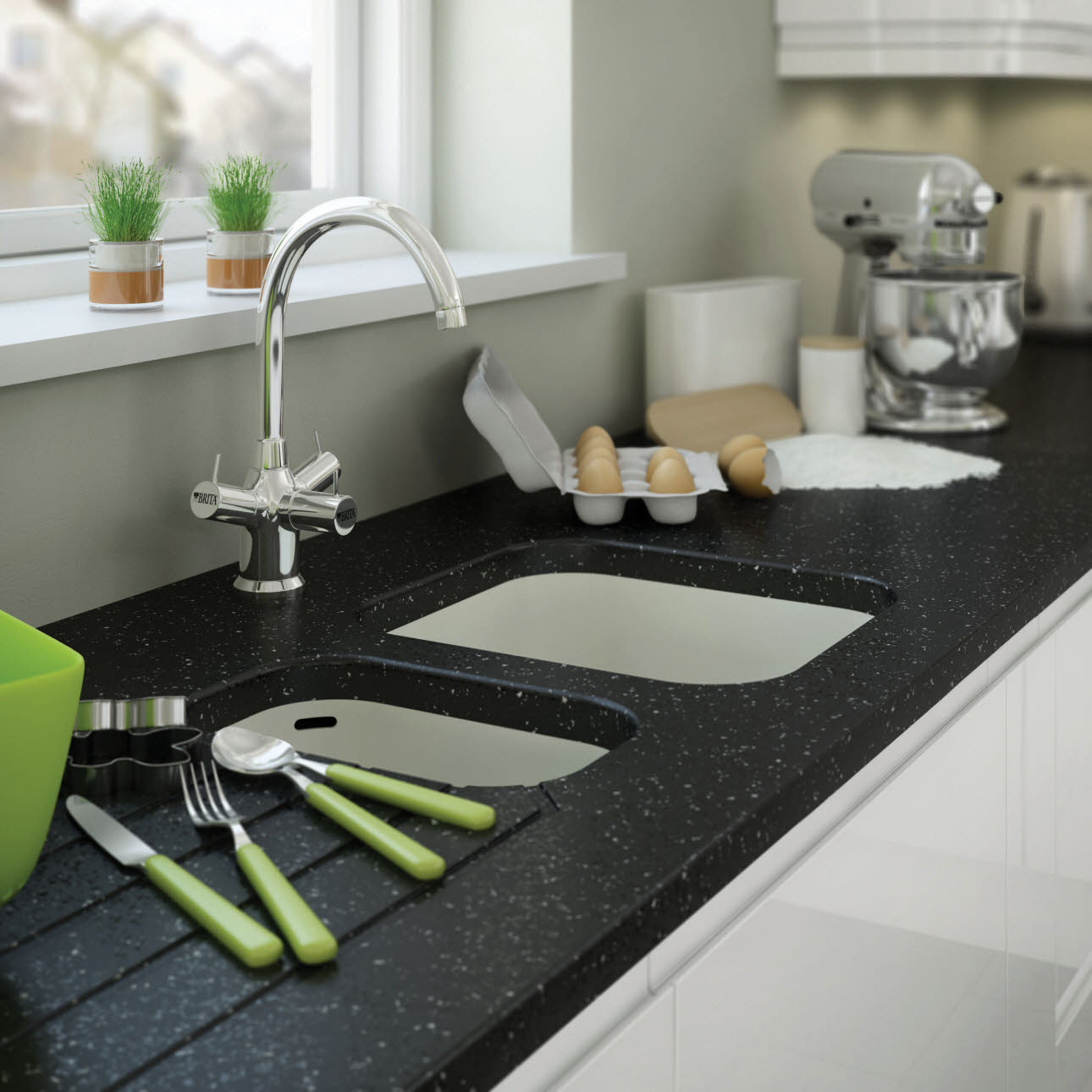 Close up of sink built into granite worktop and white kitchen unit, with cutlery