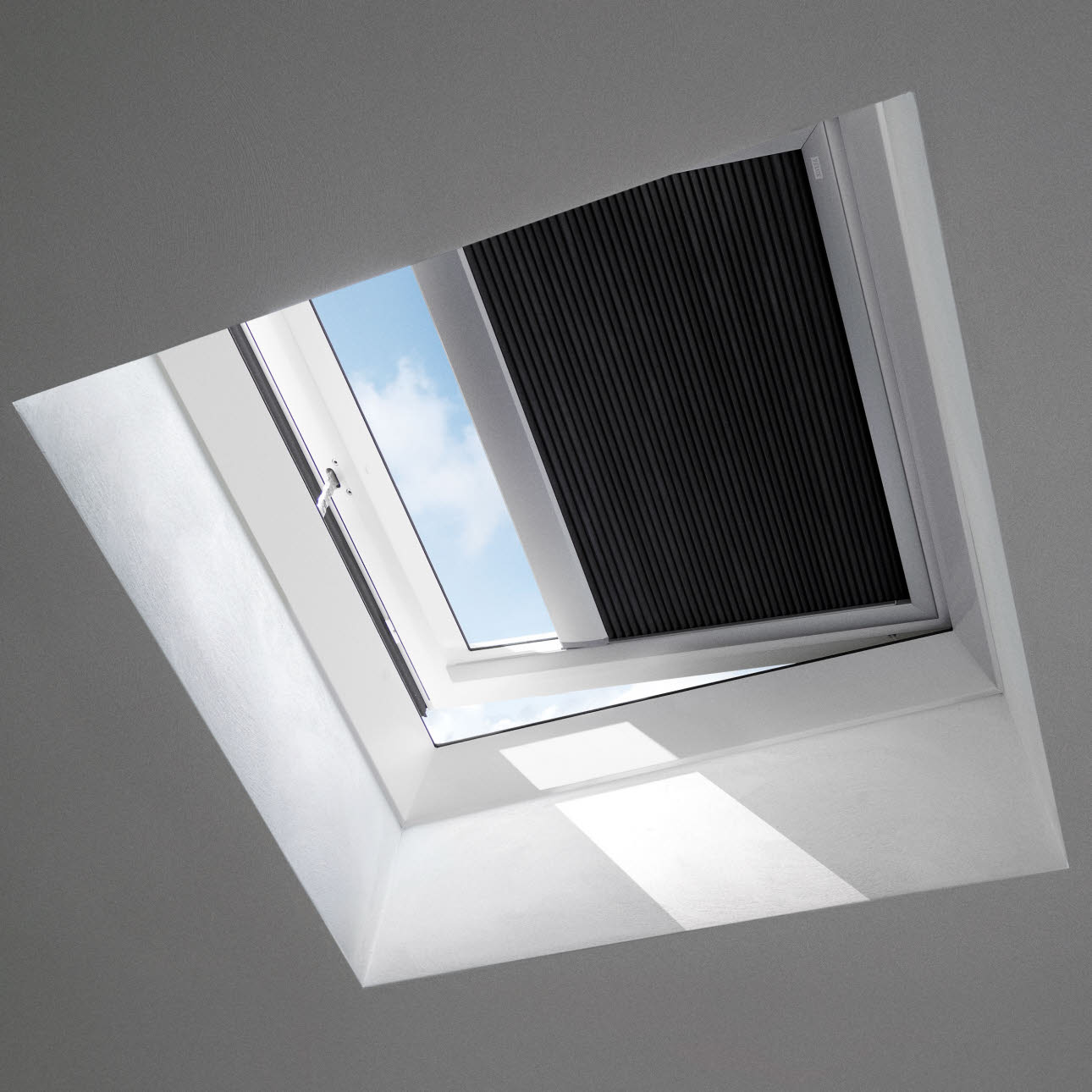 Flat roof Velux window with black blind, interior shot