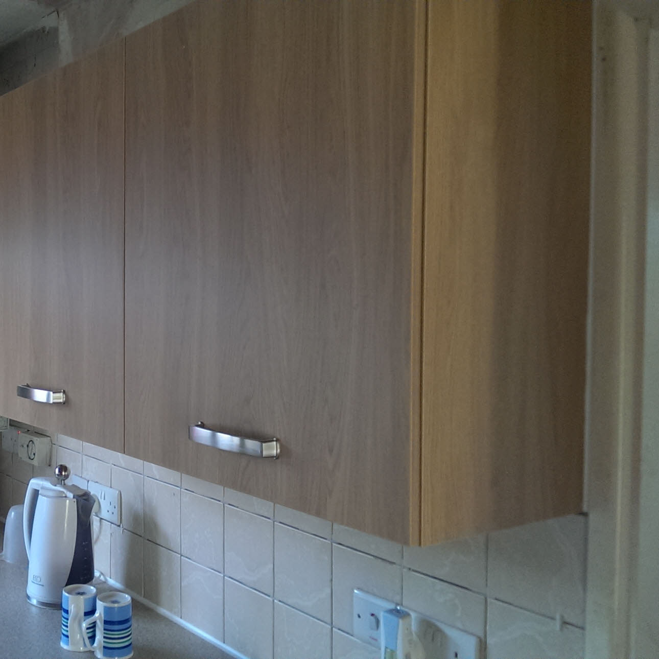 Wooden kitchen wall cupboard fitted on white tiled wall